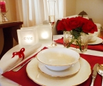 Romantic dinner with glass block tealight candle holders and glass vase with roses