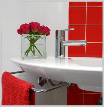 Glass block vase with red roses on bathroom sink
