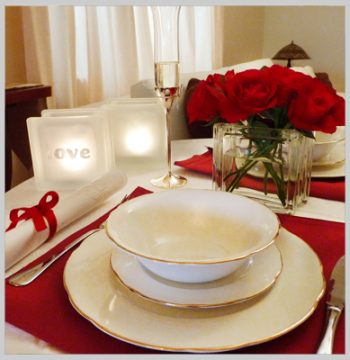 Romantic dinner setting with glass block tealights and vase with red roses
