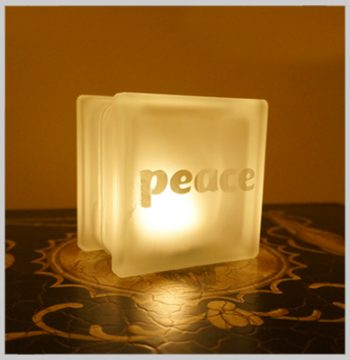 Glass block glass tealight candle holder with peace motif